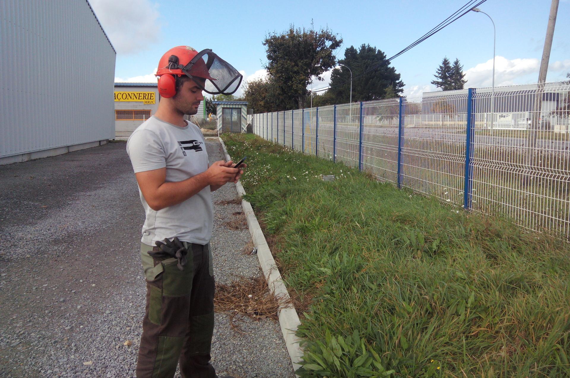 Ouvrier paysagiste utilisant une application mobile